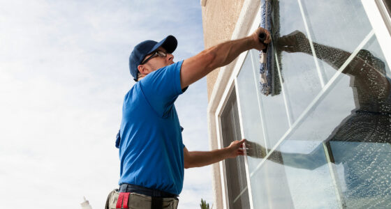 Ein Mann putzt ein Fenster von außen.