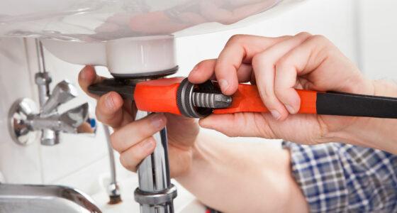 Ein Waschbecken wird mit einem Werkzeug repariert.