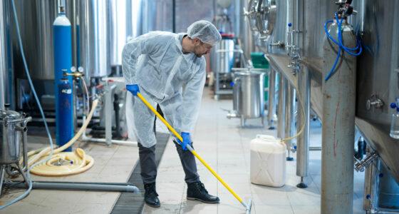 Ein Mann in Schutzkleidung reinigt den Boden einer Industriehalle.