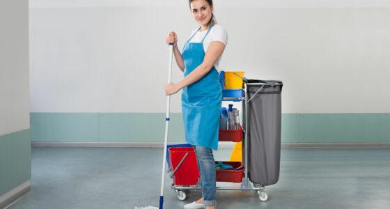 Eine lächelnde Reinigungsfachkraft steht mit einem Mop in der Hand vor ihrem Reinigungswagen.