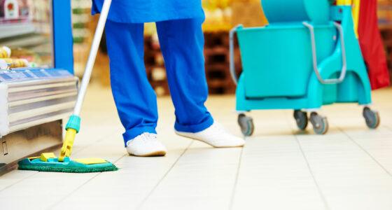 Eine Reingungsfachkraft säubert den Boden eines Supermarktes mit einem Mop.