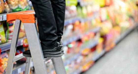 Jemand steht im Supermarkt auf einer Leiter und räumt Waren ein..