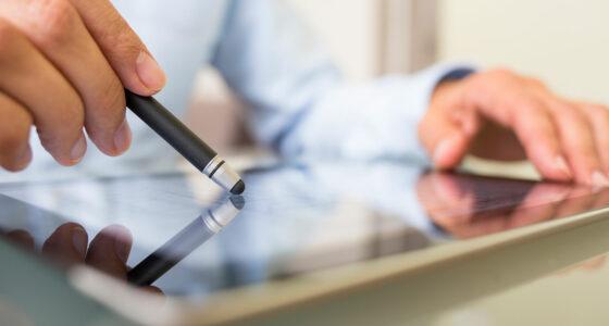 Hände, die einen Touchscreen mit Stift bedienen.