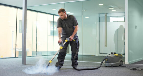 Ein Mann behandelt den Teppich eines Büros mit einem Dampfreiniger.