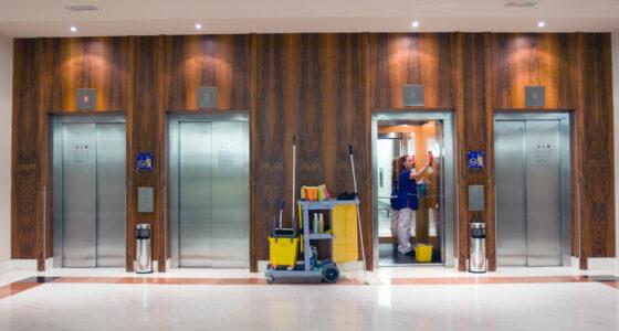 Eine Reinigungsfachkraft reinigt einen Aufzug von innen.